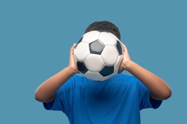 Jeu de sport. garçon en tshirt de sport bleu tenant un ballon de football au niveau de la tête de son visage n'est pas visible