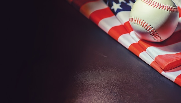 Jeu de sport traditionnel américain. base-ball. concept. balle de baseball et battes sur une table avec drapeau américain.