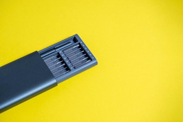 Un jeu de tournevis avec embouts dans un étui sur fond jaune. copyspace, outils pour le travail