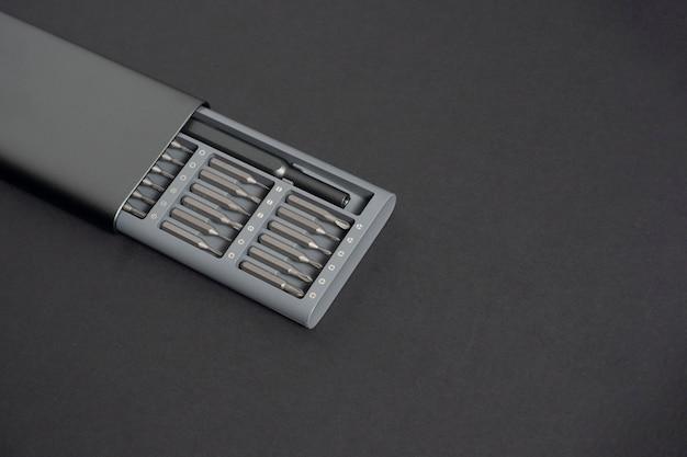Un jeu de tournevis avec embouts dans un étui sur fond sombre. gros plan, pour le travail, espace de copie, espace pour le texte