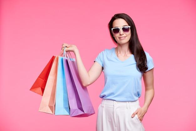 Jeune accro du shopping élégant dans des lunettes de soleil et des vêtements décontractés se vantant de ses achats tout en tenant un tas de sacs en papier sur un mur rose