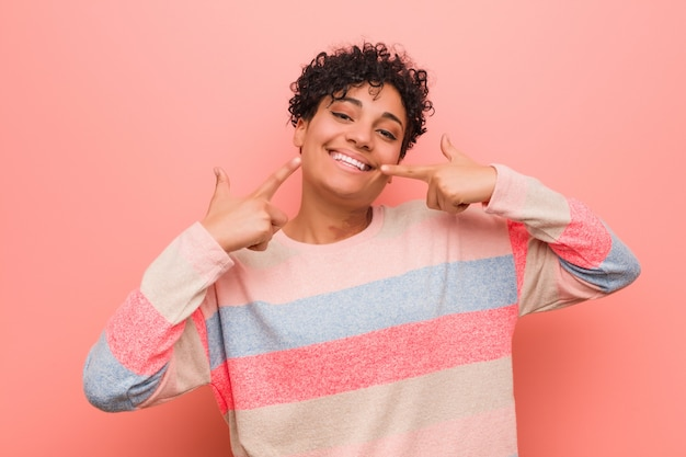 Jeune adolescent afro-américain mixte sourit, pointant les doigts vers la bouche.