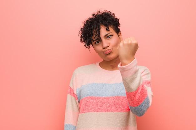 Jeune adolescent afro-américaine mixte montrant le poing à la caméra, expression faciale agressive.