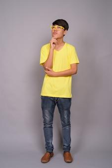 Jeune adolescent asiatique portant une chemise jaune et des lunettes contre le mur gris