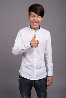 Jeune adolescent asiatique portant des vêtements décontractés intelligents contre le mur gris