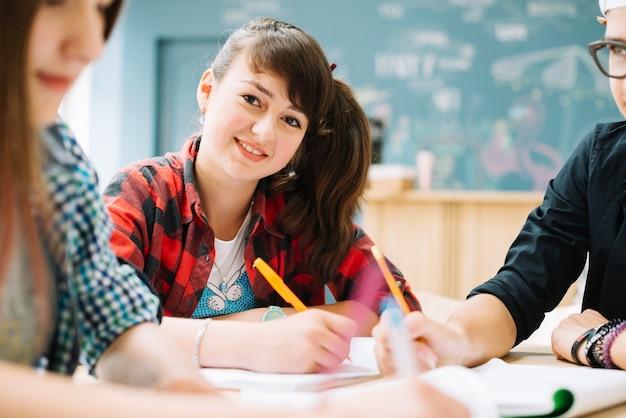 Jeune adolescent assis avec des camarades de classe à la table