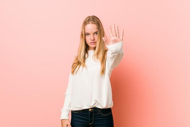 Jeune adolescent blonde femme debout avec la main tendue montrant le panneau d'arrêt, vous empêchant.