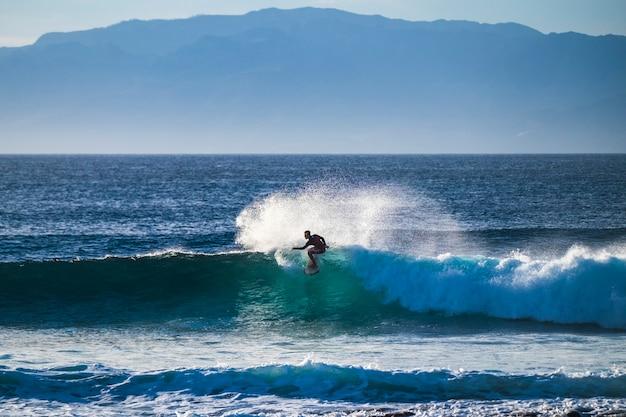 Un jeune adolescent caucasien apprend à surfer sur une grosse vague de houle dans l'océan bleu et propre dans un endroit tropical