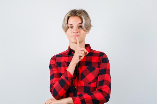 Jeune adolescent en chemise à carreaux gardant le doigt sur le menton et ayant l'air confiant, vue de face.