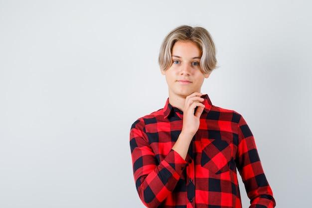 Jeune adolescent en chemise à carreaux gardant la main sous le menton et l'air confiant, vue de face.