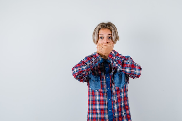 Jeune adolescent en chemise à carreaux avec les mains sur la bouche et à l'air agité
