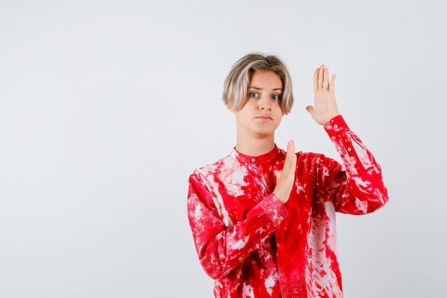 Jeune adolescent en chemise essayant de se bloquer avec les mains et ayant l'air effrayé, vue de face.