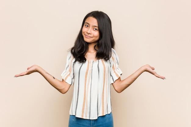 Jeune adolescent chinois mignon jeune femme blonde portant un manteau contre un mur rose, doutant et haussant les épaules en remettant en question le geste.