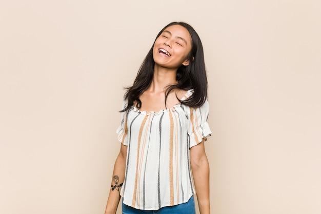 Jeune adolescent chinois mignon jeune femme blonde portant un manteau contre un rire rose détendu et heureux, cou tendu montrant les dents.