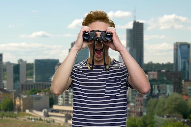 Un jeune adolescent choqué regarde à travers des jumelles. paysage urbain en arrière-plan.