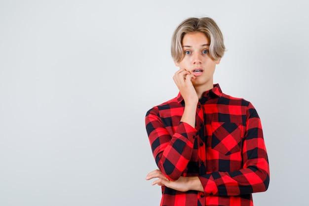 Jeune adolescent debout dans une pose de réflexion en chemise à carreaux et l'air perplexe, vue de face.