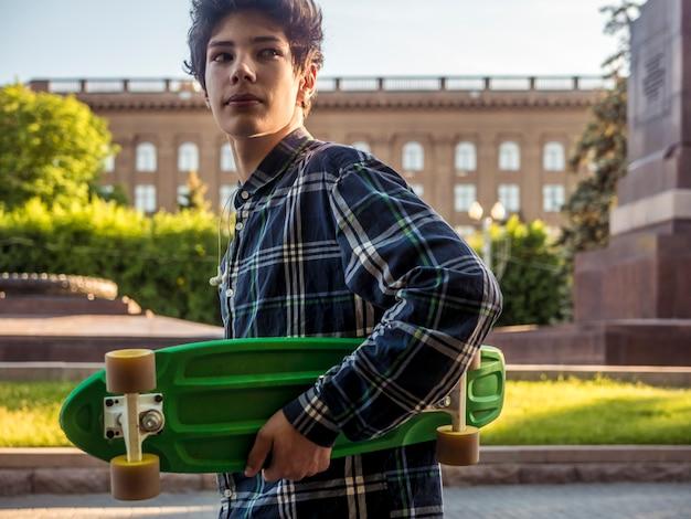 Jeune, adolescent, désinvolte, marche, penny, skateboard, dans ville