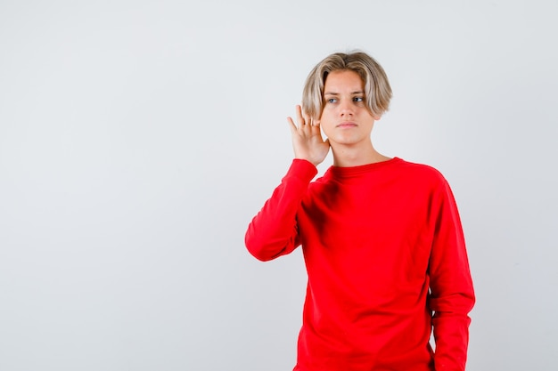 Jeune adolescent entendant une conversation privée en pull rouge et ayant l'air confus. vue de face.