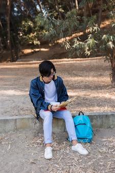 Jeune adolescent ethnique étudiant dans le parc