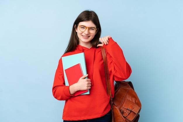 Jeune adolescent étudiant fille tenant une salade sur le mur bleu fier et satisfait de lui-même