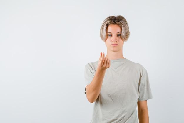 Jeune adolescent faisant un geste d'argent en t-shirt et ayant l'air sensible. vue de face.