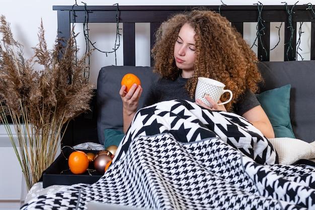 Jeune adolescent femme buvant une tasse de café et manger des fruits en position couchée dans son lit après le réveil le matin