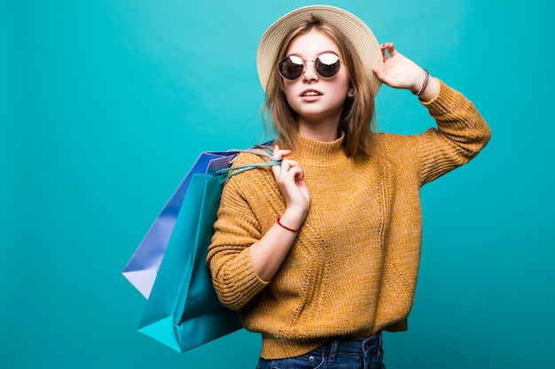 Jeune adolescent femme à lunettes de soleil et chapeau tenant des sacs à provisions dans ses mains se sentir si heureux isolé sur mur vert