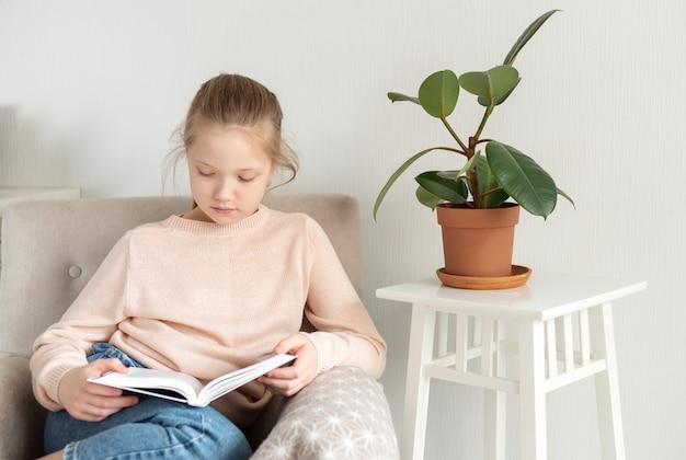 Jeune adolescent fille lisant un livre à la maison. enseignement à distance, enseignement à domicile. concept d'auto-isolement