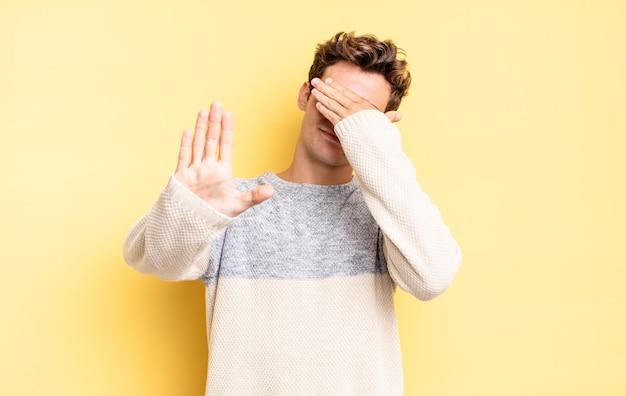 Jeune adolescent garçon couvrant le visage avec la main et mettant l'autre main devant pour arrêter l'appareil photo, refusant des photos ou des images