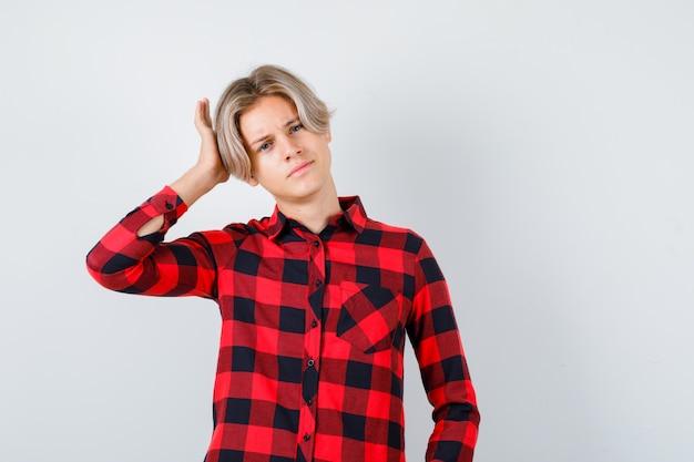Jeune adolescent gardant la main sur la tête en chemise à carreaux et l'air confiant, vue de face.