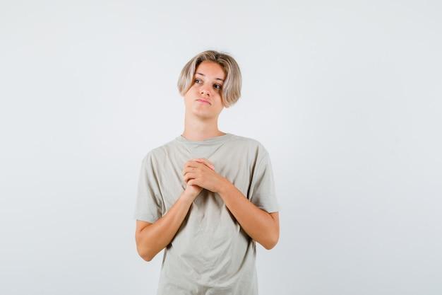 Jeune adolescent gardant les mains jointes sur la poitrine, levant les yeux en t-shirt et l'air plein d'espoir. vue de face.