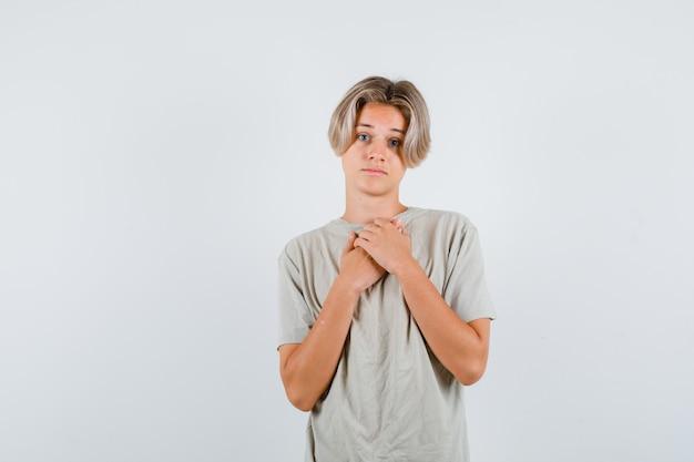 Jeune adolescent gardant les mains sur la poitrine en t-shirt et ayant l'air déçu, vue de face.