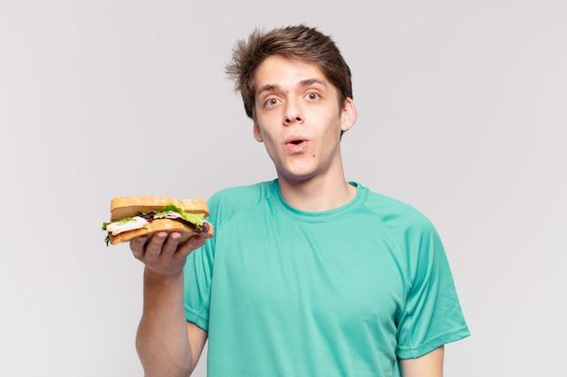 Jeune adolescent homme expression effrayée et tenant un sandwich