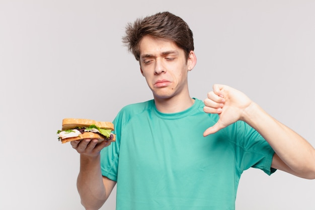 Jeune adolescent homme triste expression et tenant un sandwich