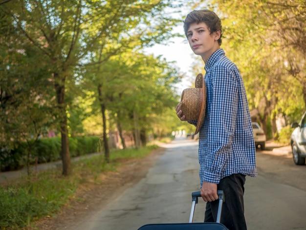 Jeune adolescent itinérant tirant une grosse valise dans la rue en été