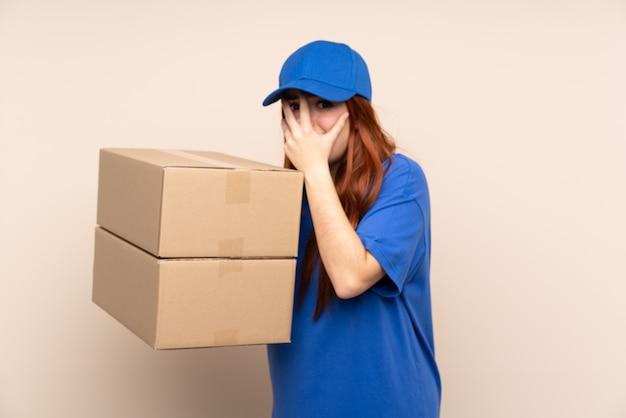 Jeune adolescent livraison femme couvrant les yeux et regardant à travers les doigts