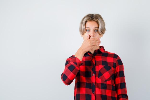 Jeune adolescent avec la main sur la bouche en chemise à carreaux et l'air surpris, vue de face.