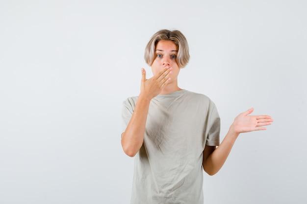 Jeune adolescent avec la main sur la bouche