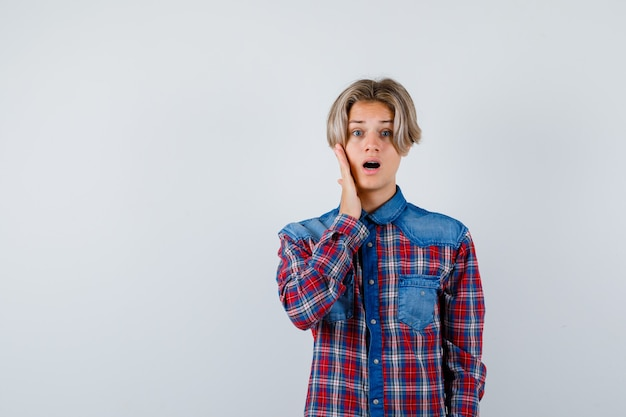 Jeune adolescent avec la main sur la joue en chemise à carreaux et à la surprise