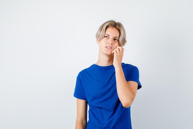 Jeune adolescent avec la main sur la joue, levant les yeux en t-shirt bleu et ayant l'air oublieux. vue de face.