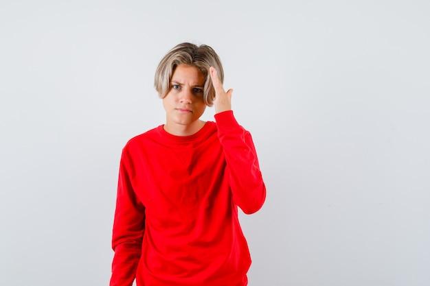 Jeune adolescent avec la main sur la tête pour voir clairement en pull rouge et l'air confus, vue de face.