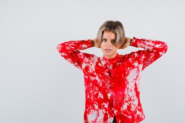 Jeune adolescent avec les mains derrière la tête en chemise et l'air sérieux. vue de face.