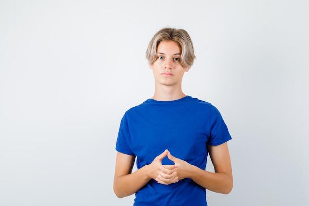 Jeune adolescent avec les mains jointes en t-shirt bleu et l'air sensé, vue de face.