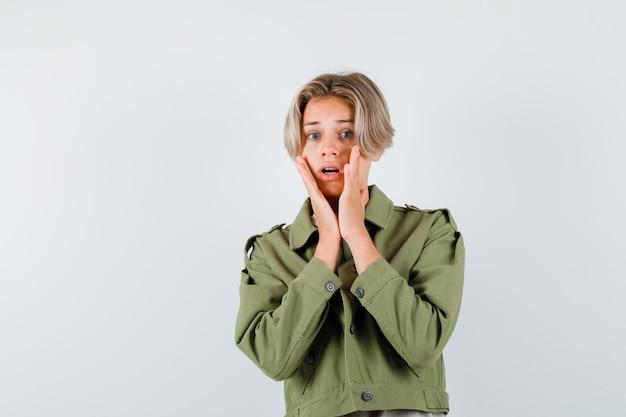 Jeune adolescent avec les mains sur les joues en veste verte et à la peur