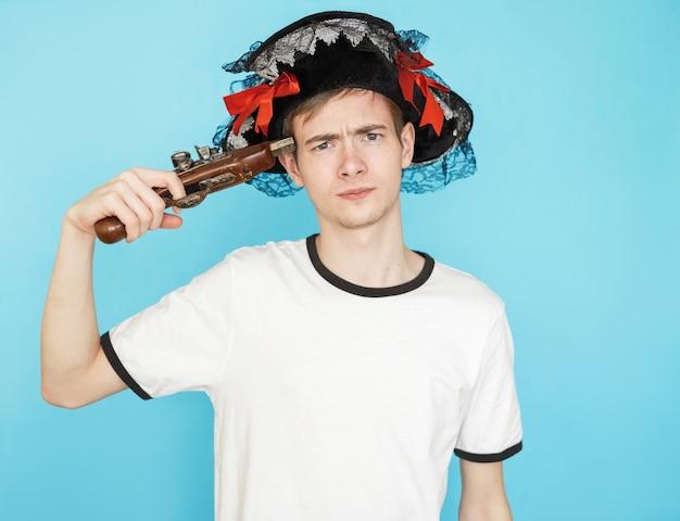 Jeune adolescent mâle drôle en t-shirt blanc sur fond bleu en chapeau de pirate et arme à la main veut tirer dans la tête