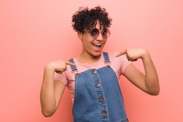 Jeune adolescent mixte afro-américaine femme surpris pointant avec le doigt, souriant largement.
