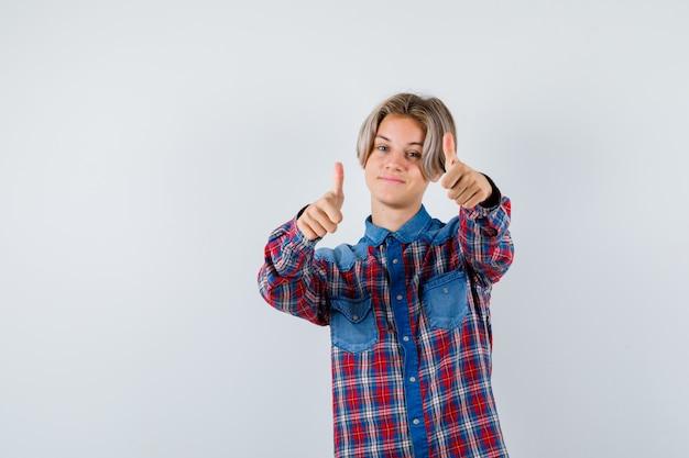 Jeune adolescent montrant le double pouce vers le haut en chemise à carreaux et l'air joyeux. vue de face.