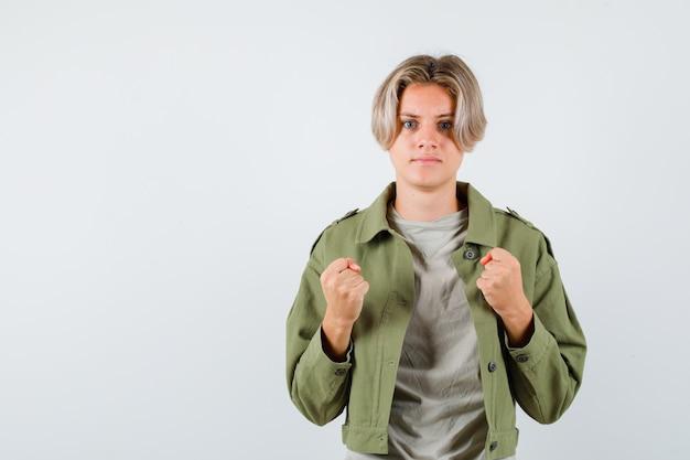 Jeune adolescent montrant les poings serrés en t-shirt, veste et semblant méchant, vue de face.