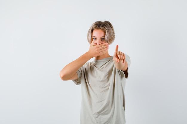 Jeune adolescent montrant tenir un geste minute, gardant la main sur la bouche en t-shirt. vue de face.