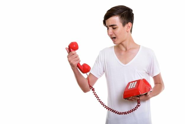 Jeune adolescent persan en colère criant au vieux téléphone